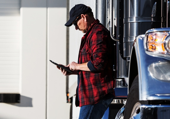 Man on tablet next to his commercial trucking vehicle